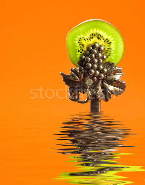 Kiwi slice clamped in luxury silver tongs in rendered water Stock photo © Nejron