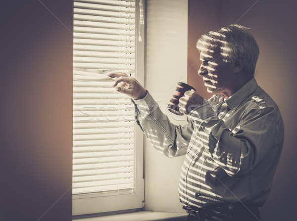 Senior man with cup looking out the window through jalousie  Stock photo © Nejron