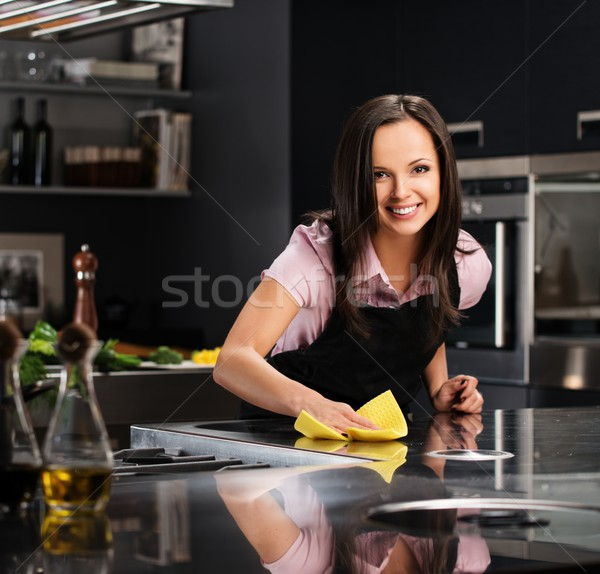 Young cheerful woman cleaning modern kitchen Stock photo © Nejron