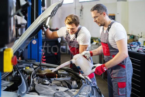 Two mechanics adding oil level in a car workshop Stock photo © Nejron