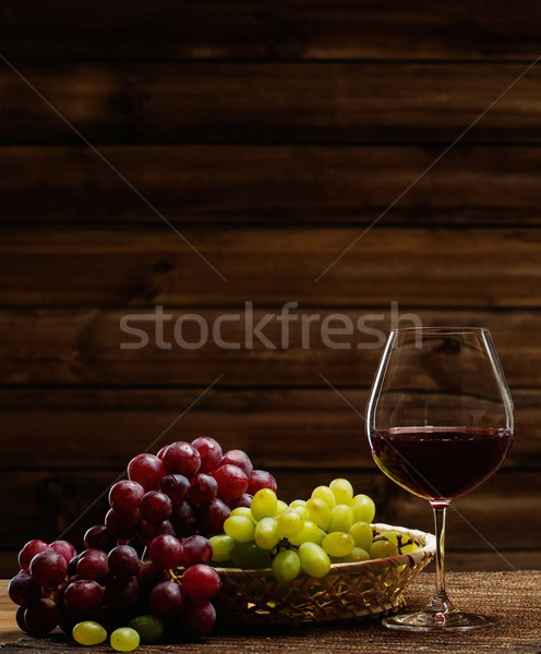 Glass of red wine and grape in basket in wooden interior  Stock photo © Nejron