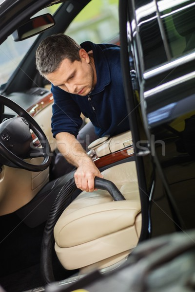 Worker on a car wash cleaning car interior with vacuum cleaner  Stock photo © Nejron