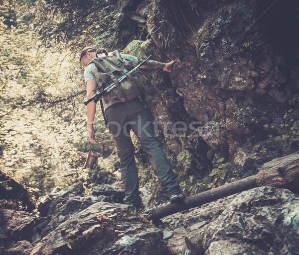 Man hiker walking across stream in mountain forest Stock photo © Nejron