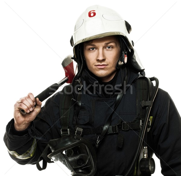 Stock photo: Young firefighter with helmet and axe isolated on white