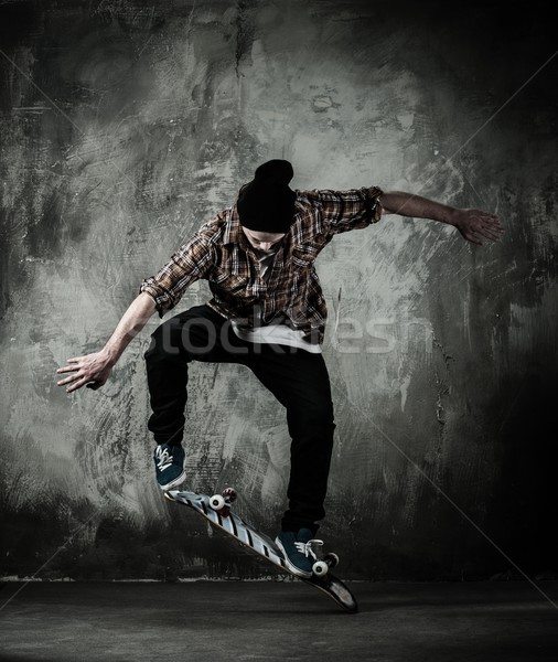 Young man in hat and shirt performing stunt on skateboard Stock photo © Nejron