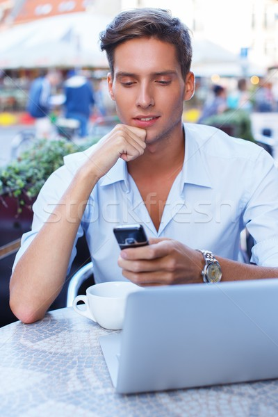Handsome young man with laptop and cup in a summer cafe Stock photo © Nejron