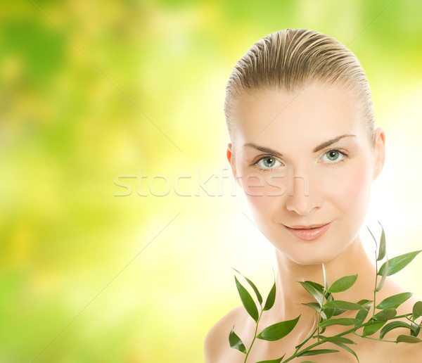 Beautiful young woman with green plant over abstract blurred bac Stock photo © Nejron