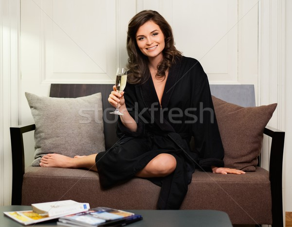 Woman in bathrobe relaxing with glass of champagne in hotel room Stock photo © Nejron
