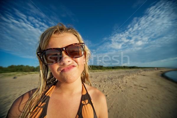 Fiatal lány tengerpart készít vicces arc felhők boldog Stock fotó © Nejron