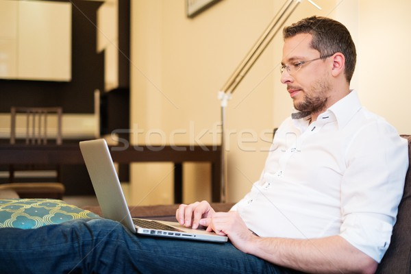 Young man with gray hair with laptop on sofa in home interior  Stock photo © Nejron