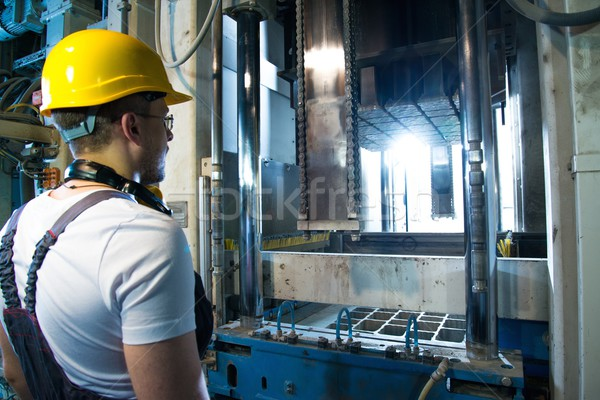 Worker in safety hat near machine on a factory Stock photo © Nejron