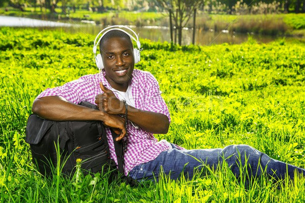 Smiling young african american man  with rucksack listens music in a park Stock photo © Nejron