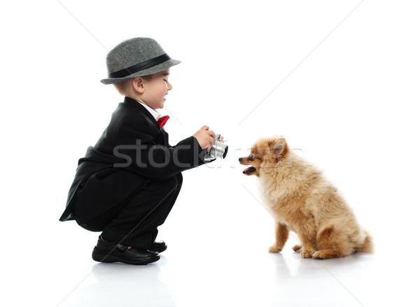 Little boy in hat and black suit with vintage camera  taking shot of little spitz Stock photo © Nejron