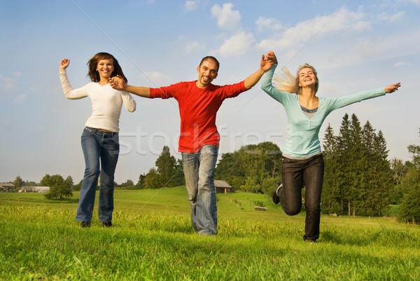 Three happy friends running outdoors Stock photo © Nejron