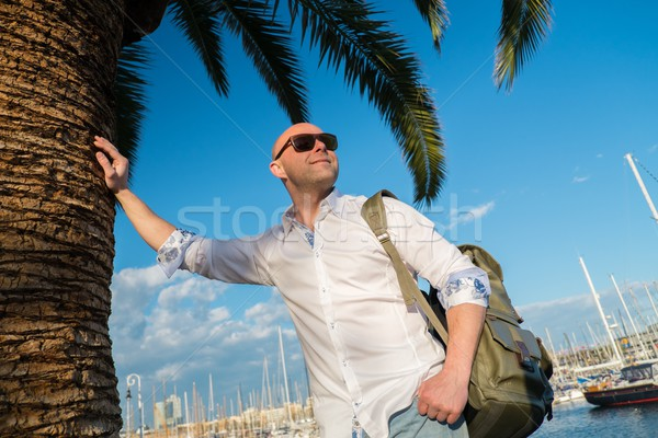 Happy middle-aged man with backpack standing near palm tree against yacht port Stock photo © Nejron