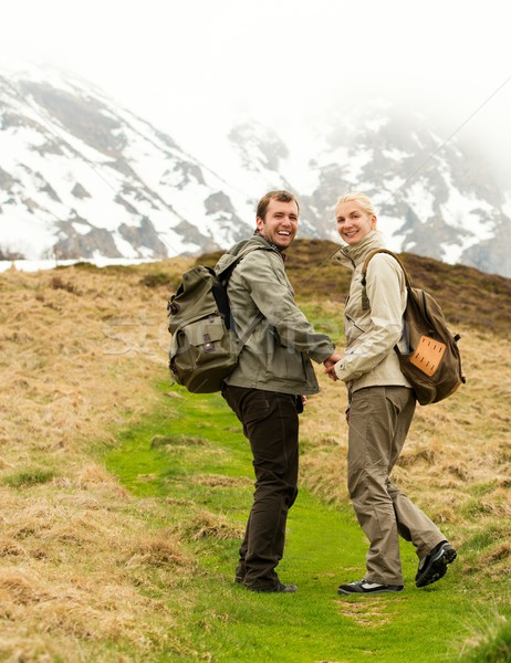 Happy young hiker couple with backpacks in mountains  Stock photo © Nejron