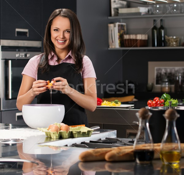 Young woman in apron breaking eggs for a dough on a modern kitchen Stock photo © Nejron