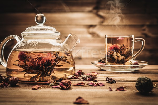 Teapot and glass cup with blooming tea flower inside against wooden background  Stock photo © Nejron