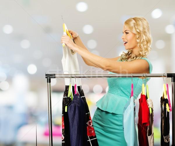 Mosolyog szőke nő választ ruhaakasztó pláza Stock fotó © Nejron