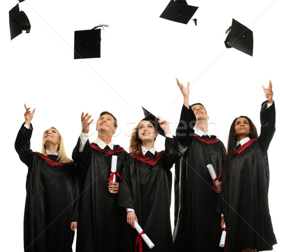 Happy multi ethnic group of graduated young students throwing hats isolated on white Stock photo © Nejron