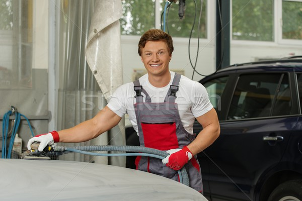 Stock photo: Young serviceman performing grinding with machine on a car bonnet in a workshop