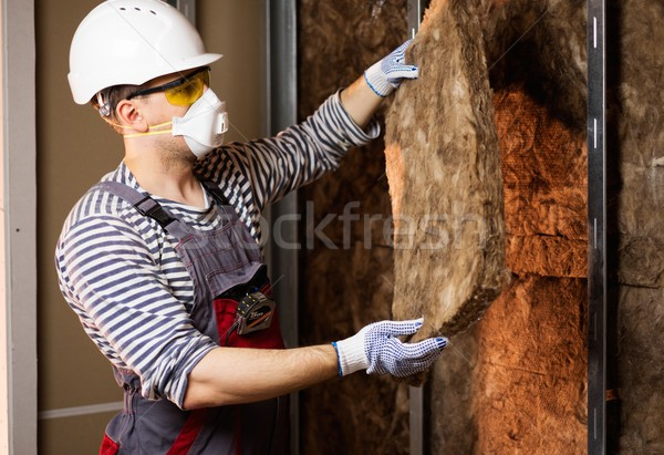 Builder in protective wear applying material on a wall Stock photo © Nejron
