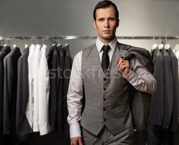 Businessman in classic vest against row of suits in shop Stock photo © Nejron