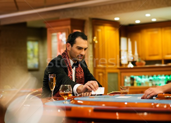 Stock photo: Young handsome man sitting behind poker table with card