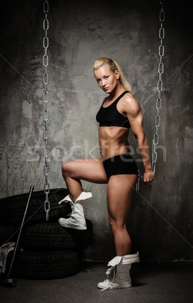 Beautiful muscular bodybuilder woman standing near stack of  tyres and holding chains  Stock photo © Nejron