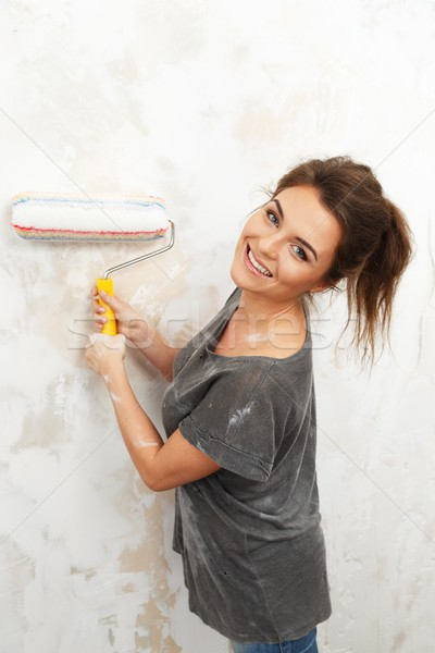 Happy beautiful young woman doing wall painting Stock photo © Nejron