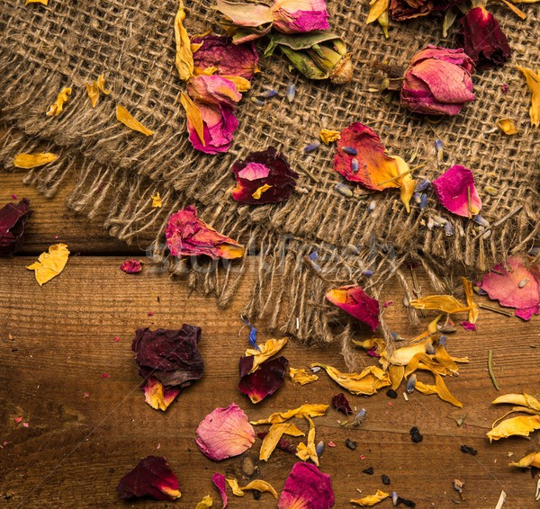 Flower tea petals on sackcloth over wooden background Stock photo © Nejron