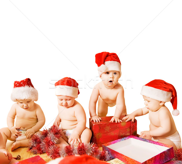 Group of adorable toddlers in Christmas hats packing presents. I Stock photo © Nejron