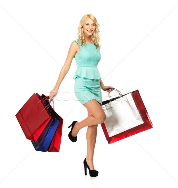 Stock photo: Smiling young blond woman on high heels with shopping bags