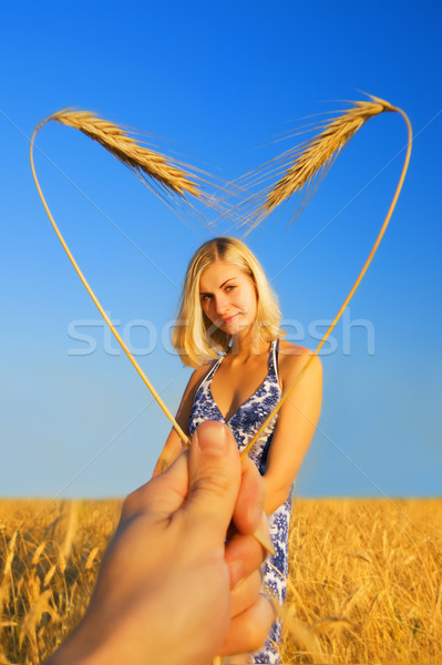 Beautiful girl standing in the wheat field and heart shaped bord Stock photo © Nejron
