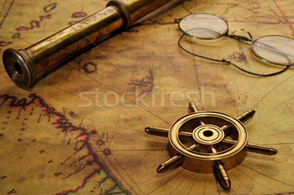 Steering wheel, glasses and spyglass on the old map Stock photo © Nejron