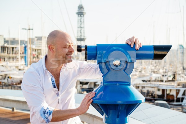MIddle-aged man looking through telescope over city panorama Stock photo © Nejron