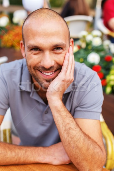 Positive middle-aged man alone behind table in summer cafe Stock photo © Nejron