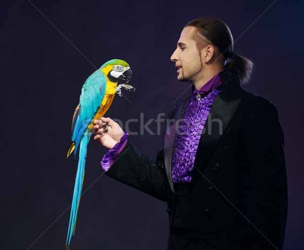 Young handsome brunette magician man in stage costume with his trained parrot Stock photo © Nejron