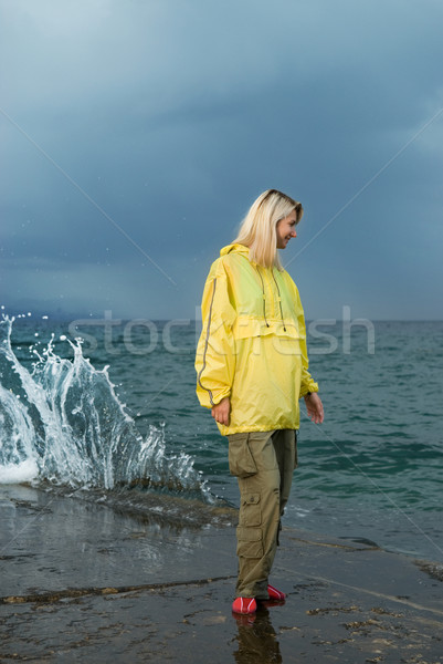 Young woman in yellow raincoat near the ocean at storm Stock photo © Nejron