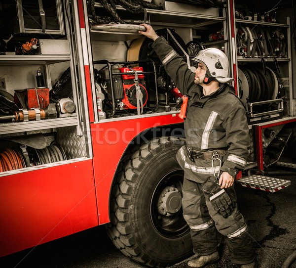 Fireman taking equipment from firefighting truck  Stock photo © Nejron