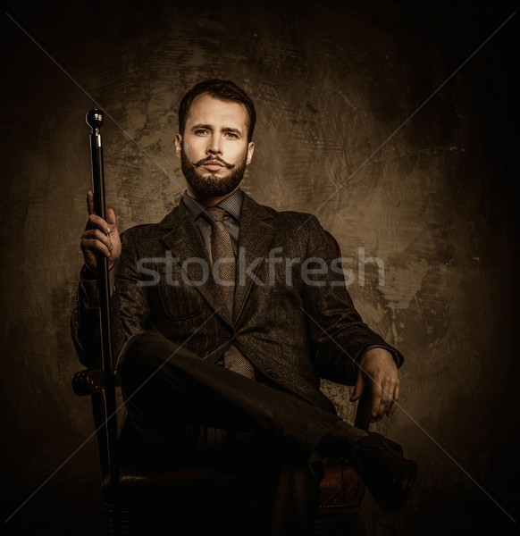 Handsome well-dressed man with walking stick sitting in leather chair  Stock photo © Nejron