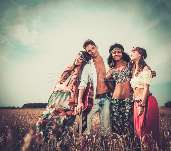 Multi-ethnic hippie friends with guitar in a wheat field  Stock photo © Nejron
