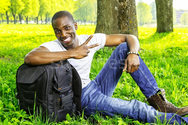 Young smiling african american man with rucksack in a park Stock photo © Nejron