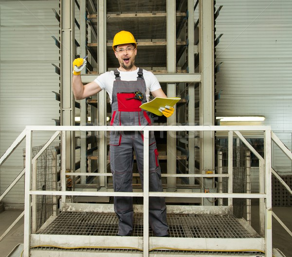 Funny worker in safety hat on a factory Stock photo © Nejron