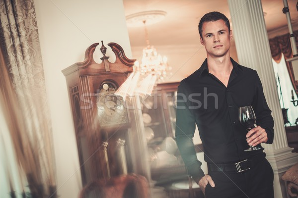 Handsome young well-dressed man in luxury house interior with glass of red wine  Stock photo © Nejron