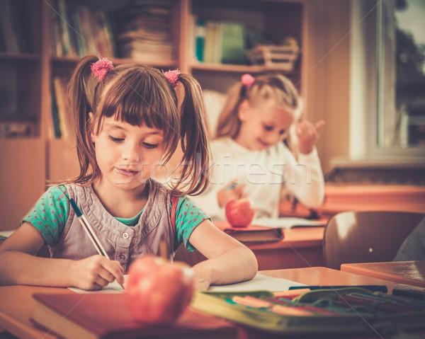 Peu écolière séance derrière école bureau Photo stock © Nejron