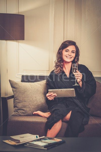 Woman in bathrobe relaxing with glass of champagne and  tablet pc Stock photo © Nejron