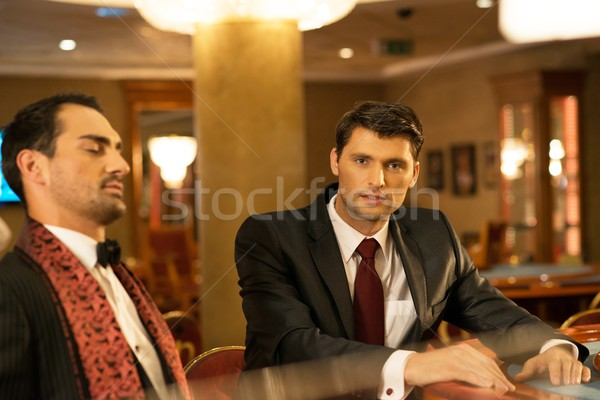 Two young well-dressed men behind gambling table in a casino Stock photo © Nejron
