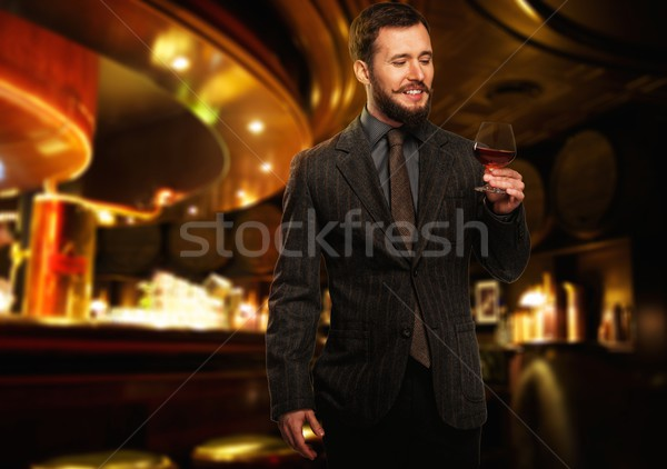 Handsome well-dressed man in jacket with glass of beverage in restaurant interior  Stock photo © Nejron