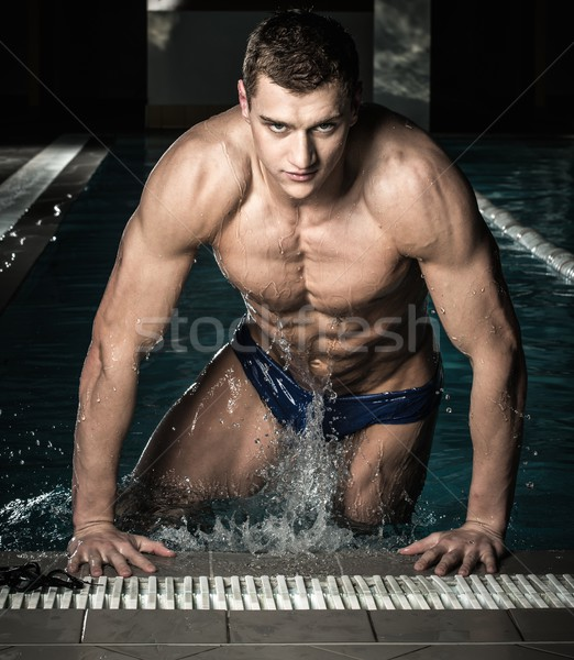 Young muscular swimmer in a swimming pool Stock photo © Nejron